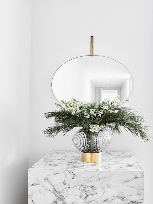 Marmortisch unter einem Spiegel mit einer Pflanze in Vase