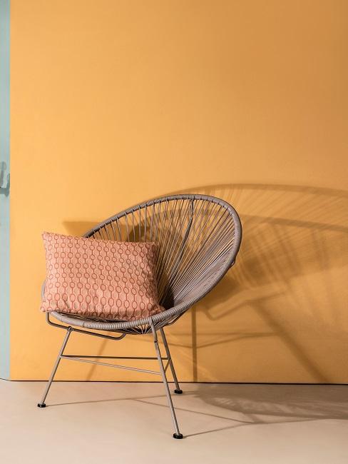 parete color curcuma e sedia in vimini con cuscino