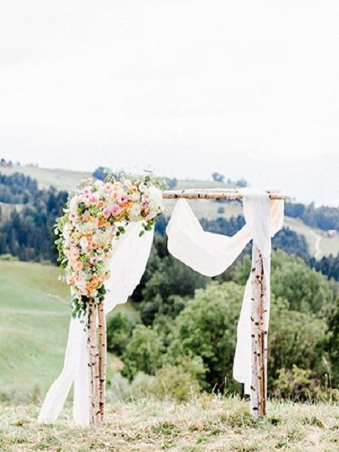 paysage rural avec un autel fait de 3 branches de bois brut decore des fleurs et de tuile blanc