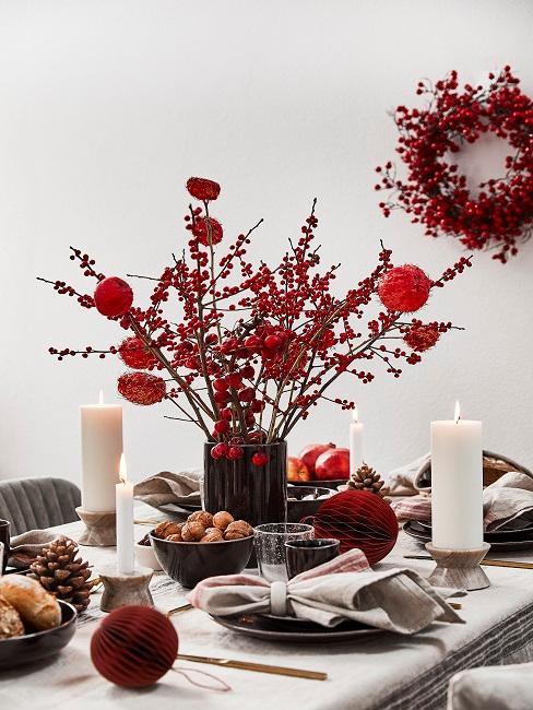 Weihnachtlich gedeckter Tisch mit Deko in Rot, Kerzen und Tannenzapfen