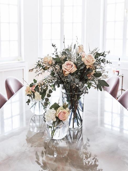 Heller langer Tisch in einem lichtdurchfluteten Raum, darauf drei klassische Vasen mit Rosensträußen in Pastellrosa