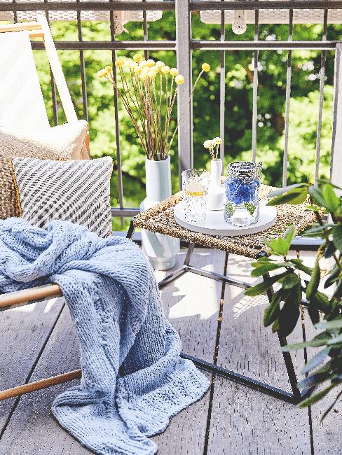 Kleiner Balok mit Beistelltisch, Stuhl, Kissen und blauer Wolldecke