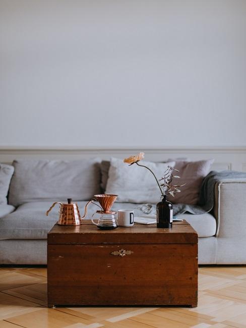 Vintage Wohnzimmer mit Sofa in hellgrau und einer großen braunen Holztruhe als Couchtisch
