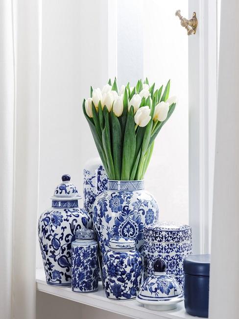 Fensterbrett mit reichlich Vasen und Porzellan-Deko in Blau Weiß und einem Tulpen-Strauß