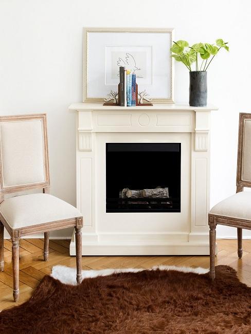 Kamin im Vintage Look zwischen alten Stühlen, davor ein Fell-Teppich in Braun