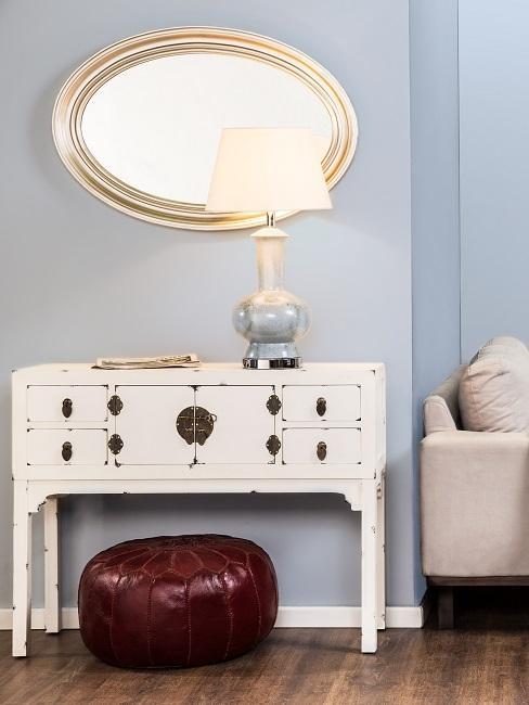 Weißes Vintage Sideboard mit Lampe im Vintage Stil, davor ein Leder-Pouf