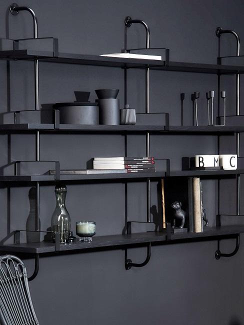 Ein schwarzes Metallregal an einer schwarzen Wand mit Dekoobjekten dekoriert.