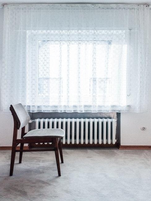 Heizungsventil tauschen brauner Sessel und weiße Vorhänge