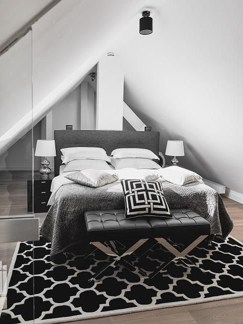 Ein Bett mit Bettwäsche in Grau-Weiß, ein Teppich davor in Schwarz-Weiß und eine Bettbank aus schwarzem Leder
