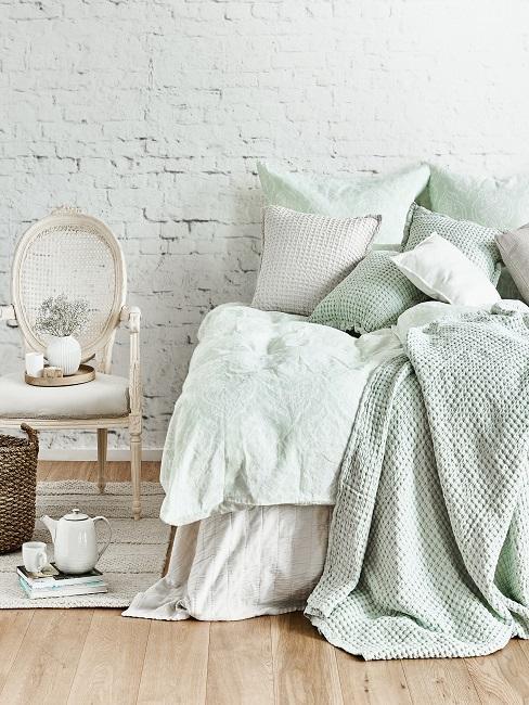 Helles Schlafzimmer im Landhausstil mit Bettwäsche in Ecru und Mint, daneben einem Stuhl aus Holz, einem Aufbewahrungskorb und einem hellbeigen Teppich