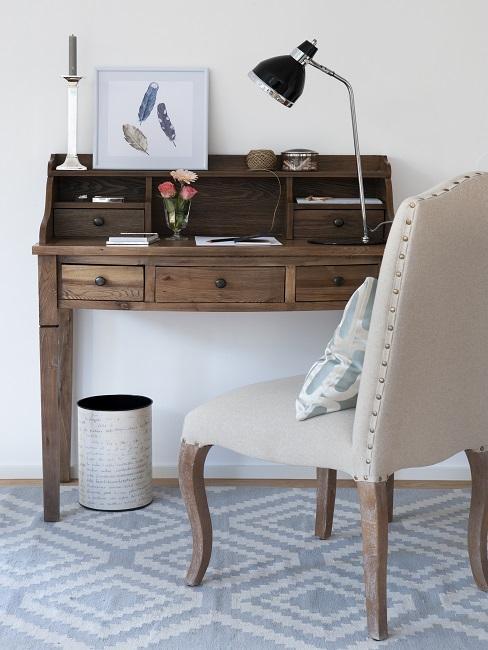 Ein heller Stuhl vor einem Vintage Schreibtisch aus Holz, darunter ein hellblauer Teppich mit Muster