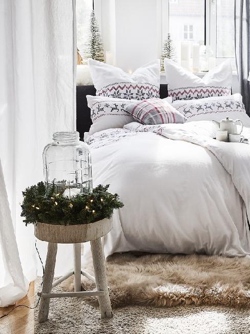 Ein Bett mit weißer Bettwäsche mit Hirschmotiv, im Hintergrund auf dem Fensterbrett und davor auf einem Holz-Beistelltisch weihnachtliche Deko im Landhausstil