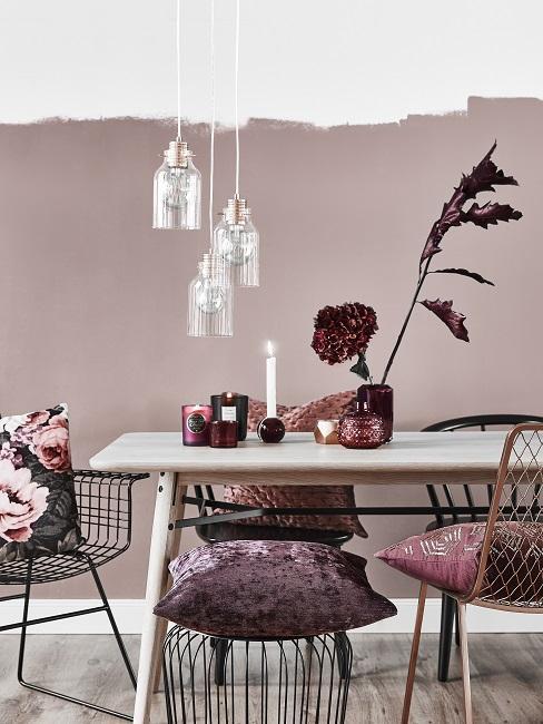 Gedeckte Farben Esszimmer in rosa und weinrot mit Holztisch, Deko, Pendelleuchte, Stühlen und Kissen