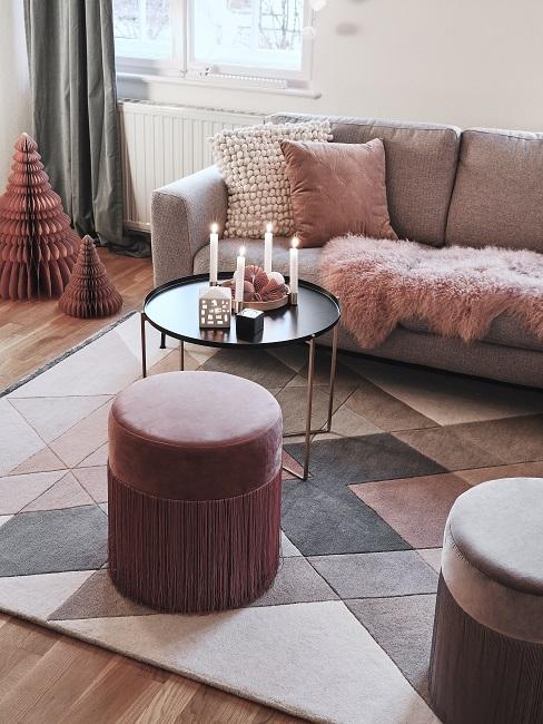 Gedeckte Farben Wohnzimmer mit Sofa, Kissen, Samthocjer und Teppich in rosa