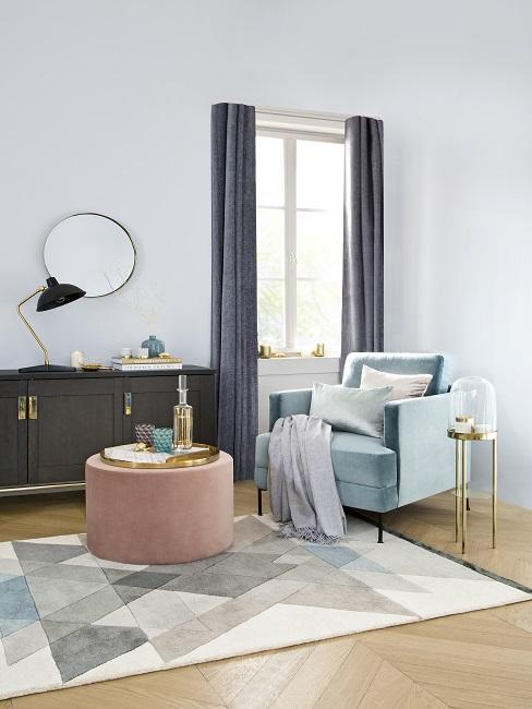 Luxus Wohnung einrichten Zimmer mit blauem Sessel, rosa Hocker, grafischem Teppich, Kommode und rundem Spiegel