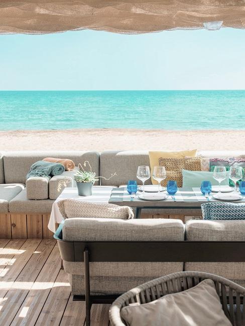 Outdoor in einem Beachclub auf Ibiza am Strand mit Meerblick, gedeckte Tische und in Grau gepolsterte Bänke