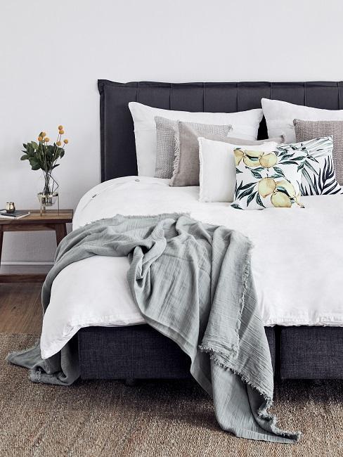 Schlafzimmer mit einem dunkelblauen Bett mit Bettwäsche aus einem leichten Material in Weiß, geeignet für den Sommer