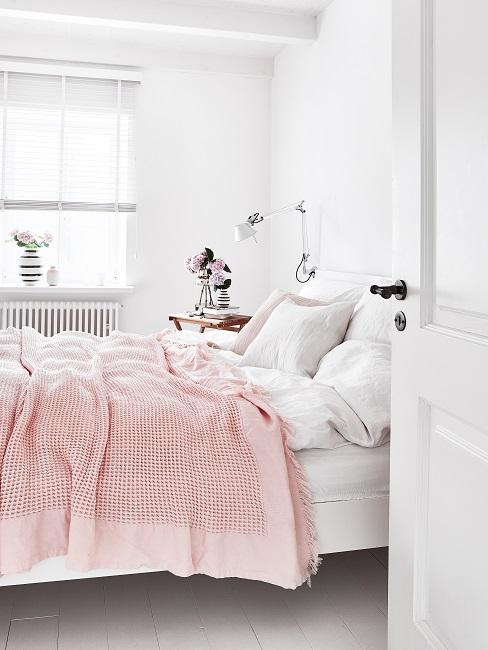 Ein weißes Bett in einem komplett weißen Raum mit weißer, ganzjährig verwendbarer Microfaser Bettwäsche und einer Tagesdecke in Rosa