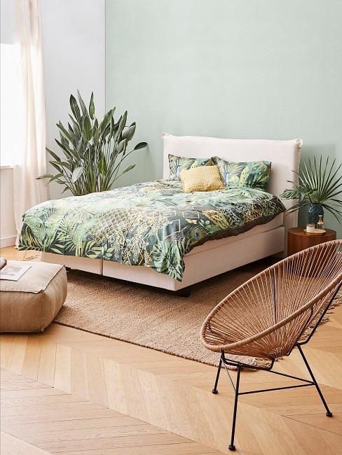 Schlafzimmer mit grüner Wand hinter dem Bettkopf und moderner Gestaltung mit Pflanzen und Rattan