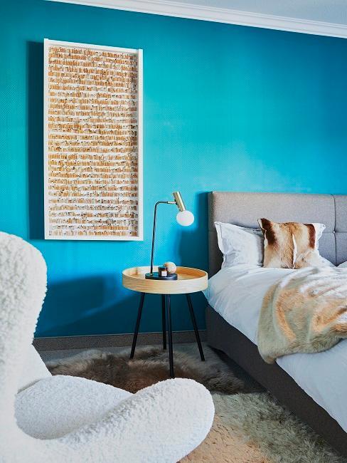 Schlafzimmer mit moderner, knallig-türkiser Wand hinter einem grauen Bett