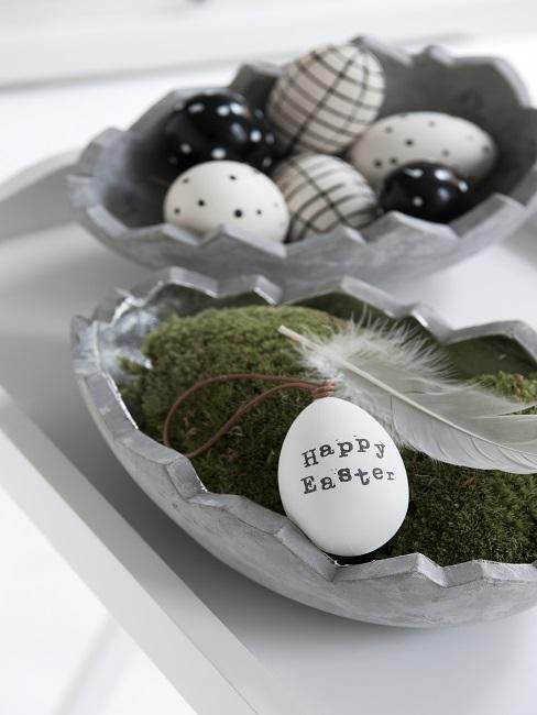 Osterdeko: Schalen in Ei-Form mit Deko-Ostereiern, eines davon mit einem Ostergruß bemalt