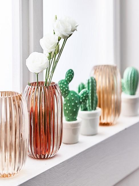 Weißes Fensterbrett mit bunten Vasen und Kaktusfiguren als Dekoration