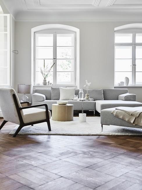 Lagom Wohntrend Wohnzimmer in grau mit Sofa, rundem Couchtisch, Sessel und großen Fenstern