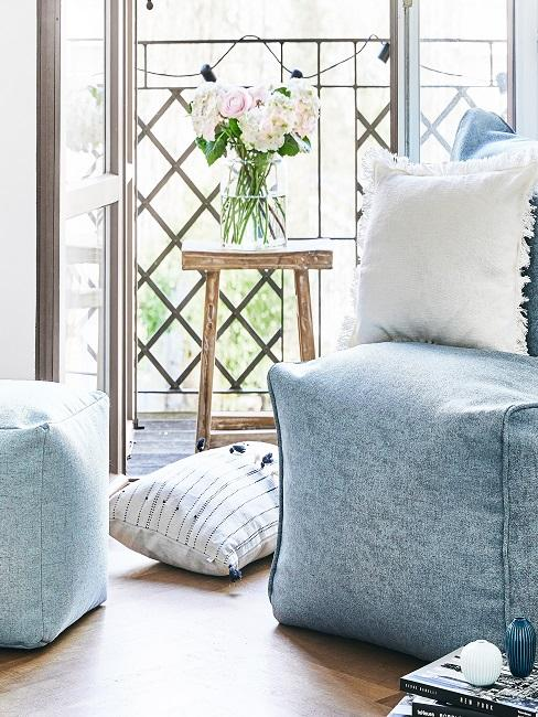 Wohnung mit einem keinen Balkon: Hellblauer Sessel und Kissen vor der offenen Balkontüre, den Balkon ziert ein kleiner Holztisch mit Vase und eine Lichterkette