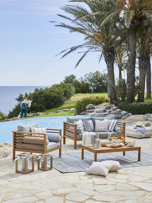 Design Garten Gartenmöbel aus Holz mit Kissen, Laternen und Teppich neben Pool