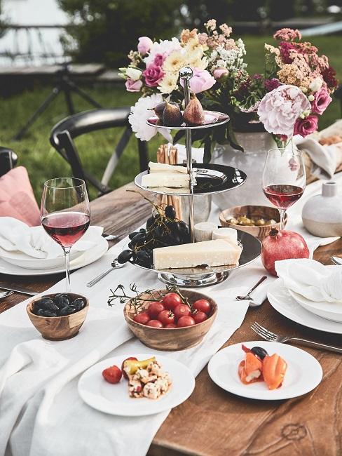 Gedeckter Tisch im Garten mit einem Etagere mit Käse und daneben einem schönen Blumenstrauß