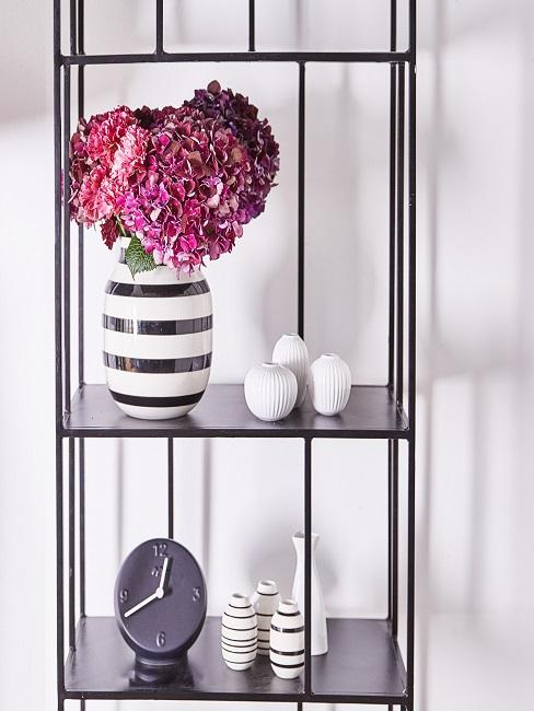 Regal aus schwarzem Metall mit einer schwarz-weiß gestreiften Vase und pinken Blumen sowie weiteren Mini Vasen und einer Uhr als Deko
