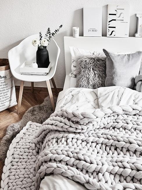 Scandi Schlafzimmer mit grauen Kissen und Plaid