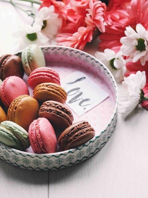 Kleines Tablett mit bunten Macarons und Zettel mit LOVE