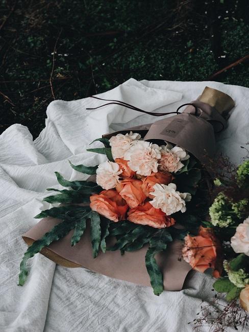 Blumenstrauß mit Rosen auf weißer Decke