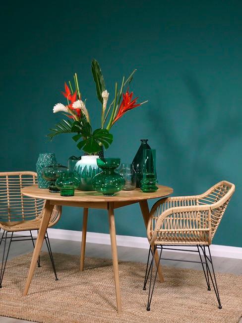 Wandfarbe Grün hiinter Holztisch und Stühlen aua Rattan