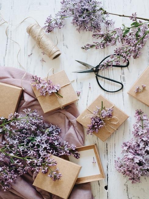 Geschenkboxen auf hellem Tisch mit Lavendel und einer Schere