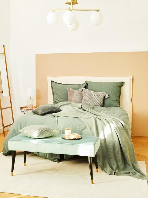 Apricotfarbene Wand in Schlafzimmer mit grüner Bettwäsche