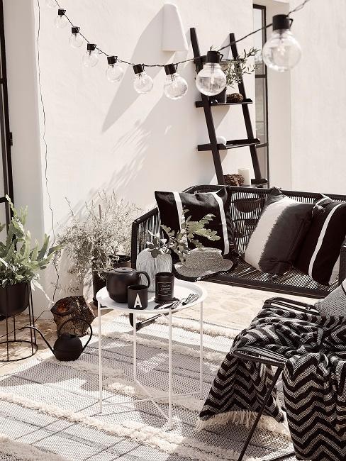 Schwarz-weißes Balkon Design mit Sofa, Tisch und Deko