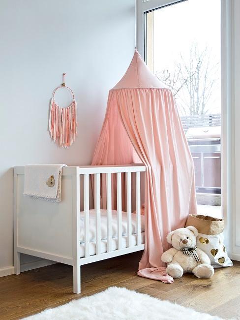 Babyzimmer einrichten für Mädchen mit weißem Babybett und rosa Baldachin