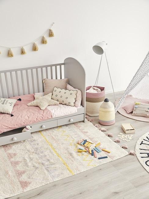 Kinderzimmer in Rosa und Gelb mit Kissen, Teppich, Girlande und Tipi