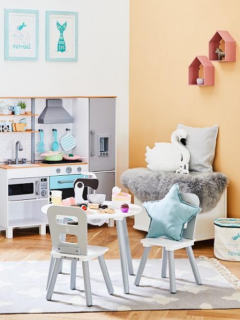 Kinderzimmer mit apricotfarbenen Wänden, Spielküche und Tischgruppe