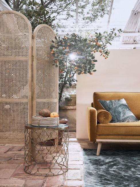 Wintergarten mit Paravent, gelbem Sofa und Beistelltisch