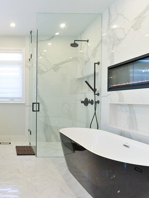 Walk-in-Dusche mit Glaskabine neben schwarzer Badewanne