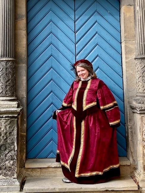 Frau in rotem Kleid vor blauer Tür