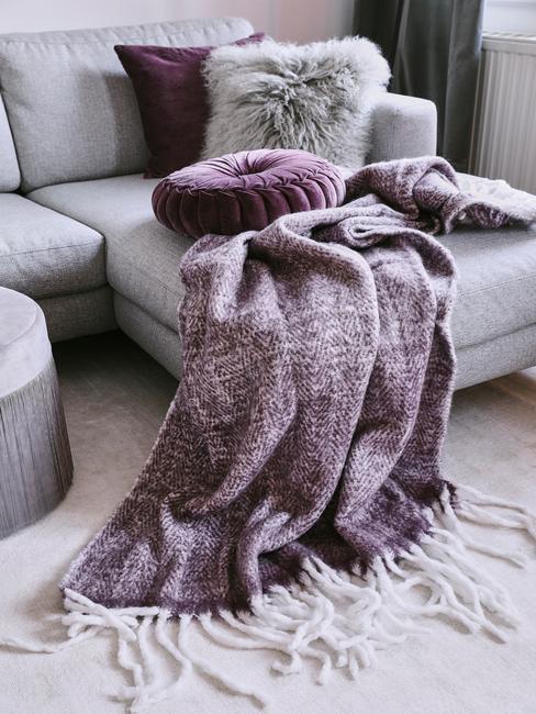 Sofá gris con manta y cojines morados