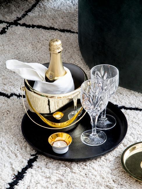 Bandeja con botella de champán y copas de cristal sobre alfombra de rayas