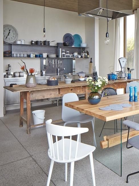 Cocina comedor estilo industrial con mesas de madera y sillas blancas