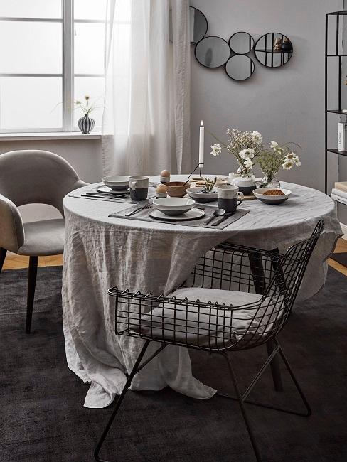 Salón comedor moderno y romántico con mesa redonda cubierta por un amplio mantel encima