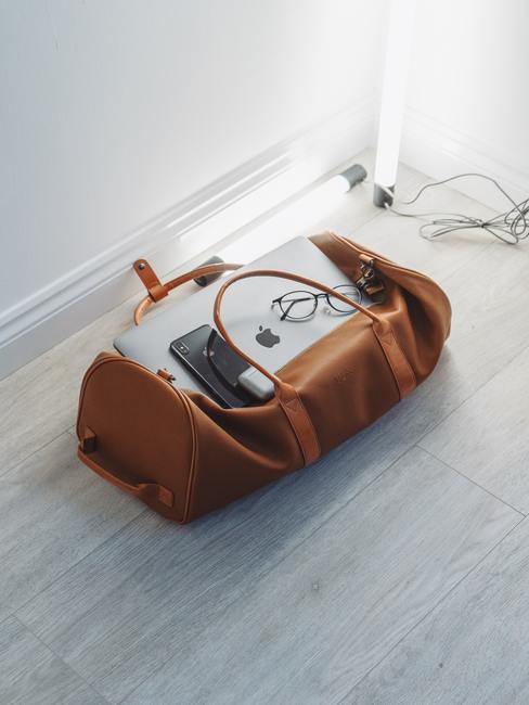 Bolso de viaje marrón en el suelo con macbook, móvil y gafas