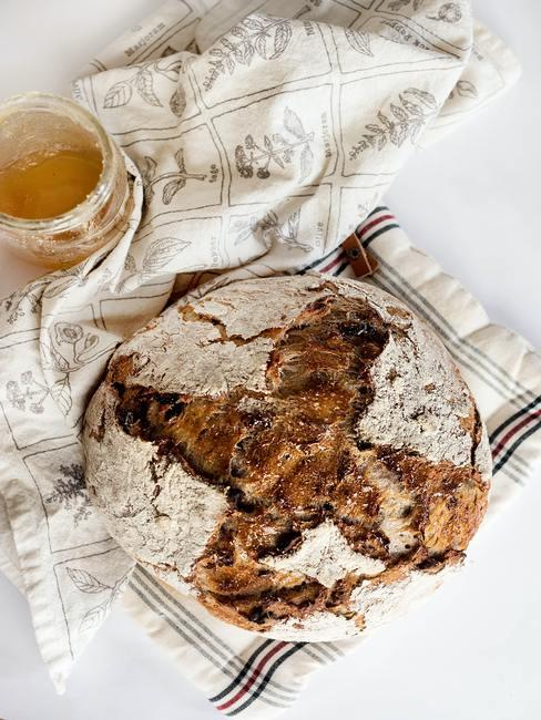 Pan casero sobre trapo de cocina y bol con miel
